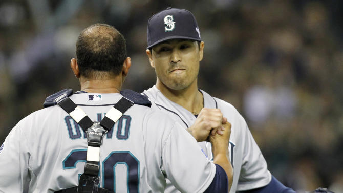 Seattle Mariners closer Brandon League celebrates with catcher Miguel Olivo after beating the Oakland Athletics 3-1 in their American League season opening MLB baseball game at Tokyo Dome in Tokyo, Wednesday, March 28, 2012. (AP Photo/Koji Sasahara)