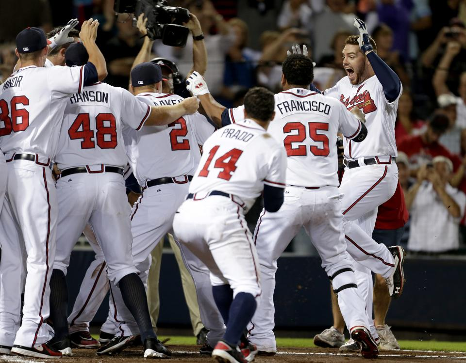 Atlanta Braves' Freddie Freeman, right, celebrates with teammates after hitting a two-run home run in the ninth inning to beat the Miami Marlins 4-3 in a baseball game Tuesday, Sept. 25, 2012, in Atlanta. The Braves clinched at least an NL wild-card berth. (AP Photo/David Goldman)
