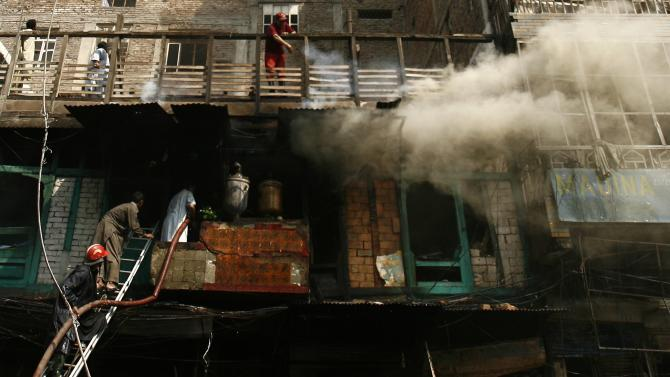 Smoke rises from the building as firefighters work to extinguish the fire at the site of a bomb attack in Peshawar