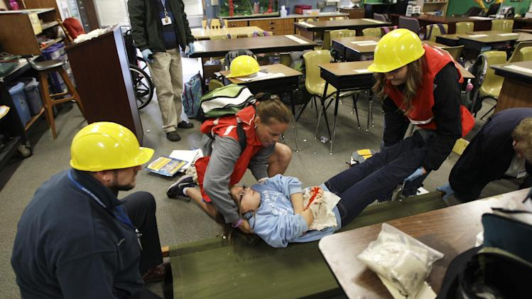 """Bella BeSerra, 9, role-plays the part of an injured student as she is lifted by P.E. teacher Kelly Miller, second from left, and health care assistant Piper Marker, right, onto a gurney as teacher Phil Schmitt looks on at left, during an earthquake drill at Twin Lakes Elementary School in Federal Way, Wash., Thursday, Oct. 18, 2012. Millions of people took part in the """"Great Shakeout"""" earthquake drill across the country and elsewhere Thursday to practice and prepare for the possibility of real quakes in the future. (AP Photo/Ted S. Warren)"""