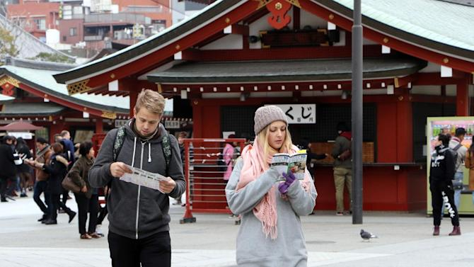 Foreign tourists looking at a guide book and a map at Sensoji temple at Tokyo's Asakusa district