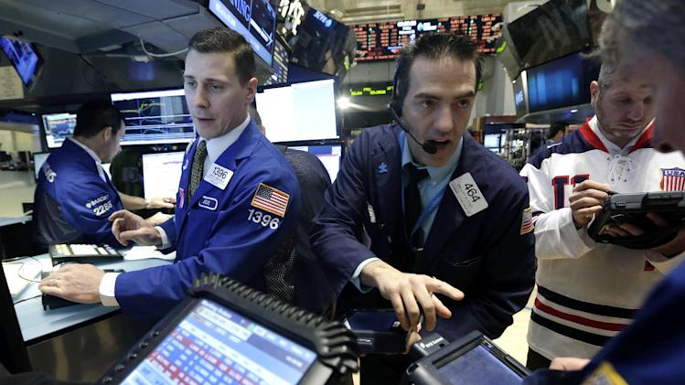 FILE - In this Friday, Feb. 21, 2014, file photo, trader Gregory Rowe, center, works at the post of specialist Joseph Mastrolia, left, on the floor of the New York Stock Exchange. The mood in financial markets steadied Monday, March 10, 2014, despite earlier big losses in Asia following disappointing Chinese and Japanese economic data. (AP Photo/Richard Drew, File)