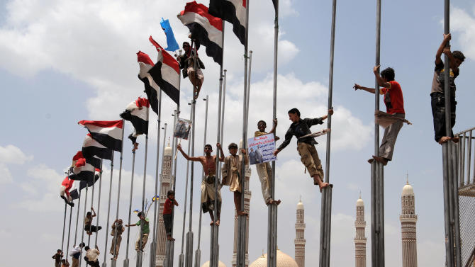 Supporters of Yemeni President Ali Abduallah Saleh, climb flag poles during a rally in Saleh' support in Sanaa, Yemen, Friday, July 15, 2011. Tribesmen killed a Yemeni army officer and two of his aides in an ambush Friday, and government shelling killed two civilians in a volatile southern area, officials said. (AP Photo/Mohammed Hamoud)
