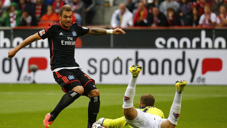 HSV Hamburg's Lasogga challenges Horn goalkeeper of FC Cologne during their German first division Bundesliga soccer match in Cologne