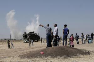 People standing on the Turkish side of the border with…