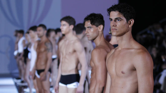 Models wear creations of Emporio Armani, from the men's Spring-Summer 2013 collection, part of the Milan Fashion Week, unveiled in Milan, Italy, Monday, June 25, 2012. (AP Photo/Luca Bruno)