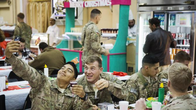 U.S. soldiers from the 3rd Cavalry Regiment pose for a photograph while eating a Christmas day lunch at forward operating base Gamberi in the Laghman province of Afghanistan