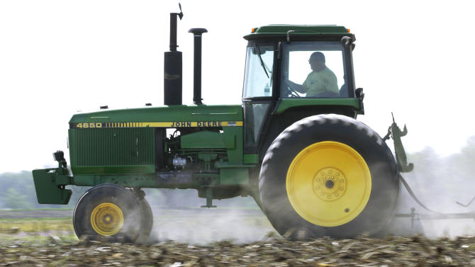 FILE - In this April 2, 2012 file photo, Derek Long uses a John Deere tractor to disk and cultivate a field in preparation for planting corn in Loami, Ill. Deere & Co. reports quarterly earnings on Wednesday, Nov. 20, 2013. (AP Photo/Seth Perlman, File)