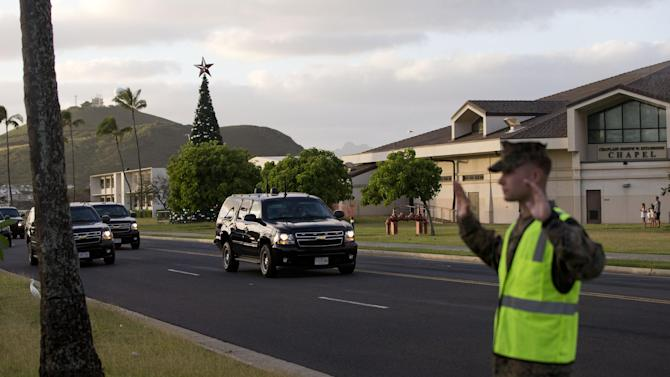 The motorcade carrying President Barack Obama passes a Marine and waving people as he heads back to his rental home after playing golf Sunday, Dec. 28, 2014, at Marine Corps Base Hawaii in Kaneohe Bay, Hawaii during the Obama family vacation. (AP Photo/Jacquelyn Martin)
