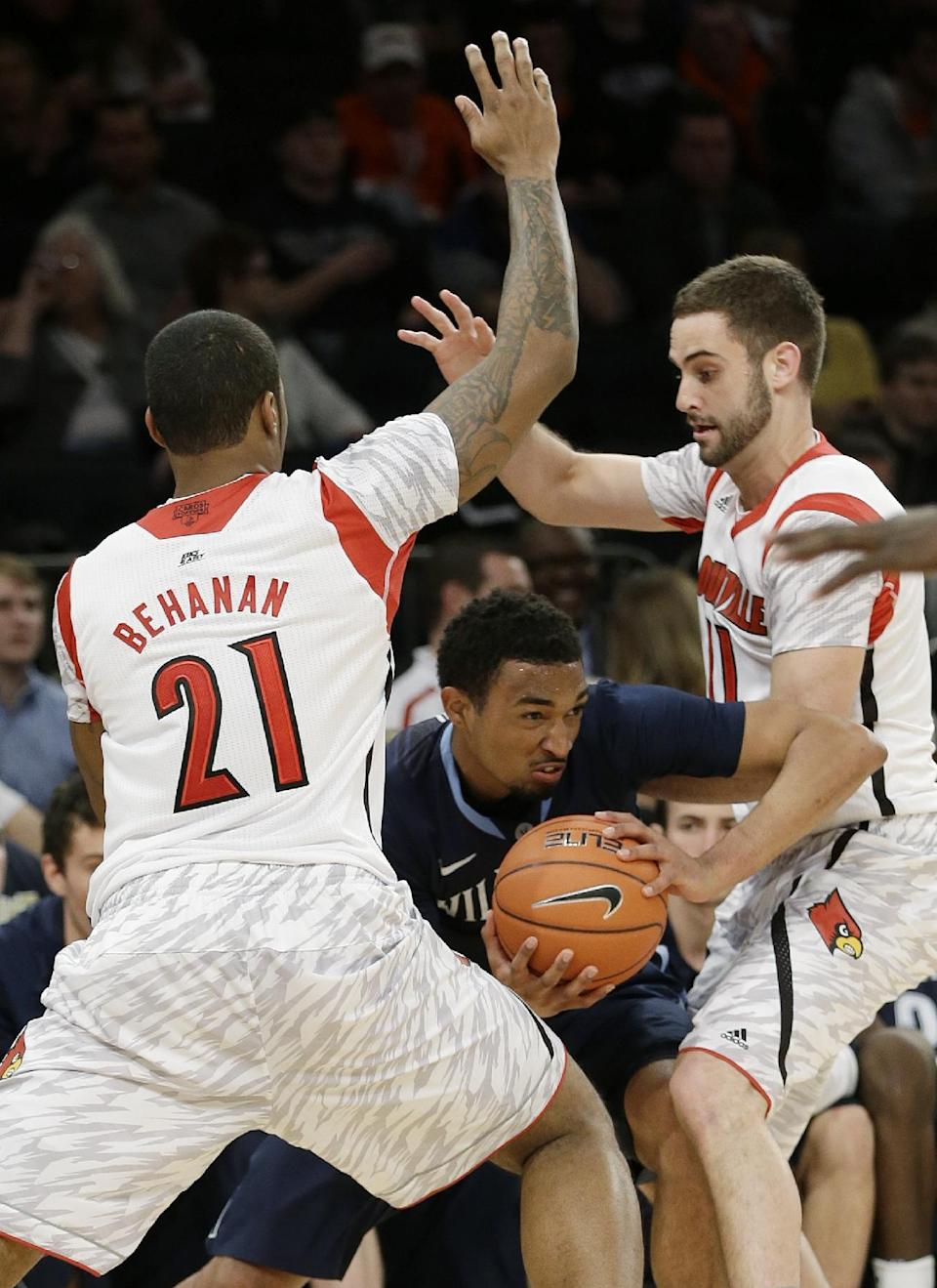 Villanova's Darrun Hilliard, center, is defended by Louisville's Luke Hancock, right, and Chane Behanan, left, during the second half of an NCAA college basketball game at the Big East Conference tournament, Thursday, March 14, 2013, in New York. (AP Photo/Frank Franklin II)
