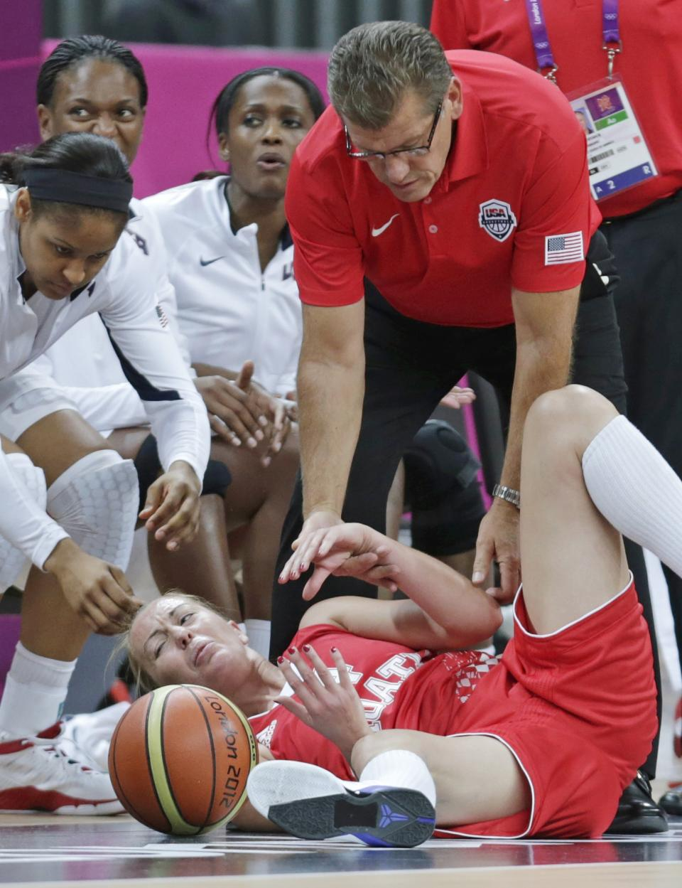 USA head coach Geno Auriemma, top, helps up Croatia guard Sandra Mandir after she was knocked out of bounds during a basketball game at the 2012 Summer Olympics, Saturday, July 28, 2012, in London. (AP Photo/Charles Krupa)