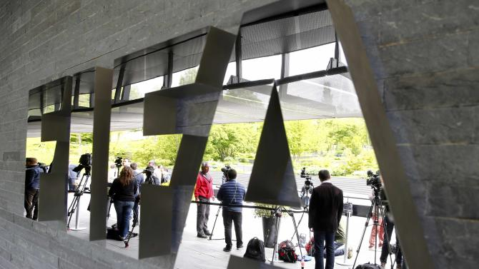 Members of the media stand in front of the FIFA headquarters in Zurich