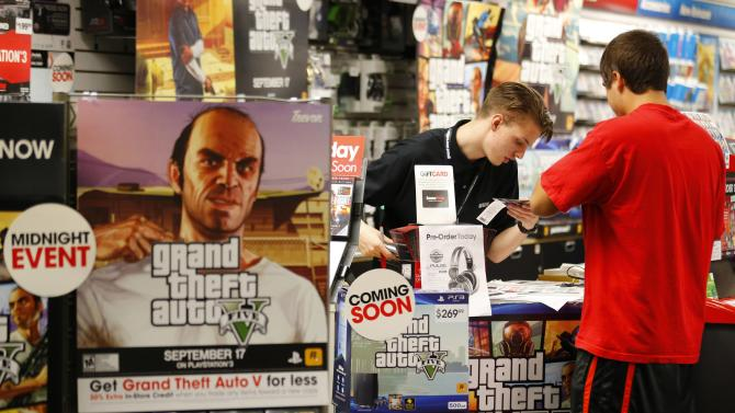 "Game enthusiasts purchase the latest release of ""Grand Theft Auto V"" after the game went on sale at the Game Stop store in Encinitas, California"