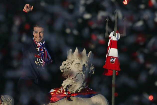 Atletico Madrid's captain Fernandez puts team scarf around neck of statue of Neptune as team celebrates their victory against Real Madrid in Spanish King's Cup final, in central Madrid