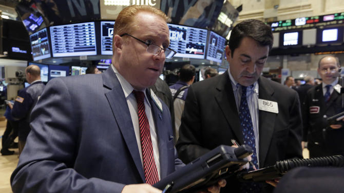 Traders Dan Ryan, left, and Mark Muller work on the floor of the New York Stock Exchange, Wednesday, Nov. 26, 2014. Stock indexes are holding near record levels as traders digest some mixed news on the U.S. economy. (AP Photo/Richard Drew)