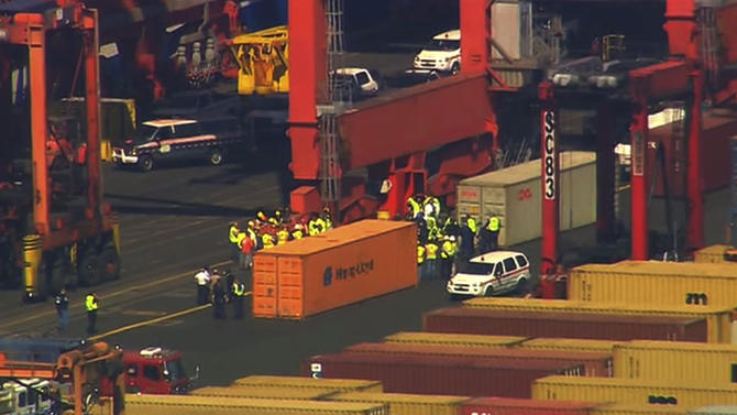 This image made from video provided by Eyewitness News WABC-TV shows an aerial view near a container ship in Newark with suspected stowaways. Dock workers rushed to unload containers stacked on top of one another inside a cargo ship that arrived in New Jersey from the Middle East on Wednesday, June 27, 2012 after Coast Guard officials heard knocking from one during a routine inspection, suggesting that stowaways might be on board. (AP Photo/Eyewitness News WABC-TV) MANDATORY CREDIT