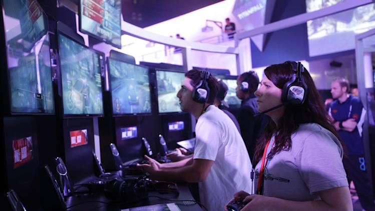 "Fanny Bouton, right, plays the ""Need for Speed"" racing video game at the EA booth during the Electronic Entertainment Expo in Los Angeles, Wednesday, June 12, 2013. (AP Photo/Jae C. Hong)"