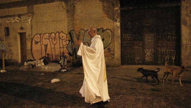 Priest Lancellotti talks with homeless people on the street about a free Christmas dinner at Sao Miguel Arcanjo church, in Sao Paulo
