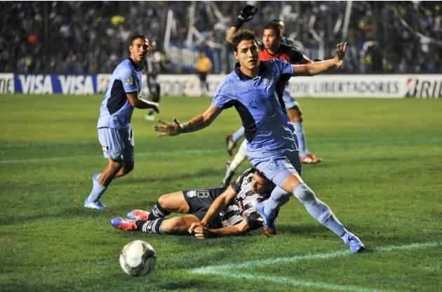 Cabrera of Bolivia's Bolivar follows the ball as Denis Stracqualursi of Ecuador's Emelec, falls down behind him during Copa Libertadores match in Guayaquil