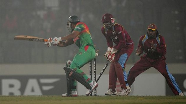 Bangladeshi batsman Mohammad Mahmudullah (L) is bowled as West Indies wicketkeeper Devon Thomas (C) and Chris Gayle (R) look on after hitting a bounderyduring the fifth one day international between Bangladesh and West Indies (AFP)