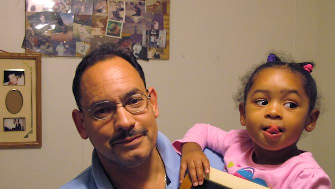 In this Sept. 20, 2012 photo, Robert Garcia holds his daughter Amara Garcia, 3, in their apartment in the Bronx borough of New York, as she displays a photograph of her grandfather Felix Garcia and his late wife. Felix Garcia is enrolled in an overnight program for dementia victims with sleep problems at the Hebrew Home at Riverdale, also in the Bronx. (AP Photo/Jim Fitzgerald)