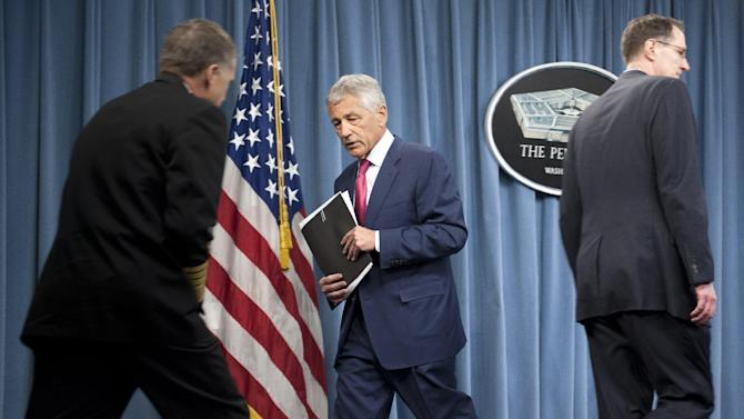 Defense Secretary Chuck Hagel, center, walks past Joint Chiefs Vice Chairman Navy Adm. James Winnefeld, left, and Defense Undersecretary for Policy James Miller, at the Pentagon, Friday, March 15, 2013, after announcing the Pentagon will spend $1 billion to add 14 interceptors to a West Coast-based missile defense system, responding to what it called faster-than-anticipated North Korean progress on nuclear weapons and missiles.  (AP Photo/Cliff Owen)