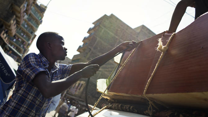 Daniel, 22, ties furniture to the roof of his car as he prepares to leave his house in the Mathare slum of Nairobi, Kenya Sunday, March 3, 2013 and head to his family's home in the countryside. Five years after more than 1,000 people were killed in election-related violence, Kenyans go to the polls on Monday to begin casting votes in a nationwide election seen as the country's most important - and complicated - in its 50-year history. (AP Photo/Mackenzie Knowles-Coursin)