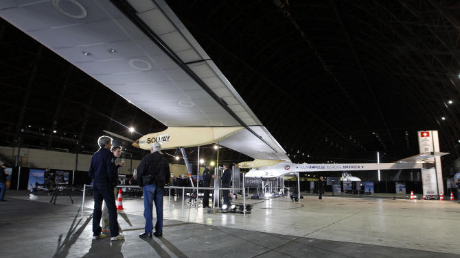 Ground crew members stand next to the Solar Impulse solar-powered plane that was on display during a press conference at Moffett Airfield, NASA Ames Research Center in Mountain View, Calif., on Thursday, March 28, 2013. A solar-powered plane that has wowed aviation fans in Europe is set to travel across the United States with stops in Phoenix, Dallas, Washington, D.C., and New York, organizers of the trip announced Thursday. The Solar Impulse is powered by about 12,000 photovoltaic cells that allow it to fly without jet fuel. It has the wing span of a commercial airplane but the weight of the average family car. (AP Photo/Tony Avelar)
