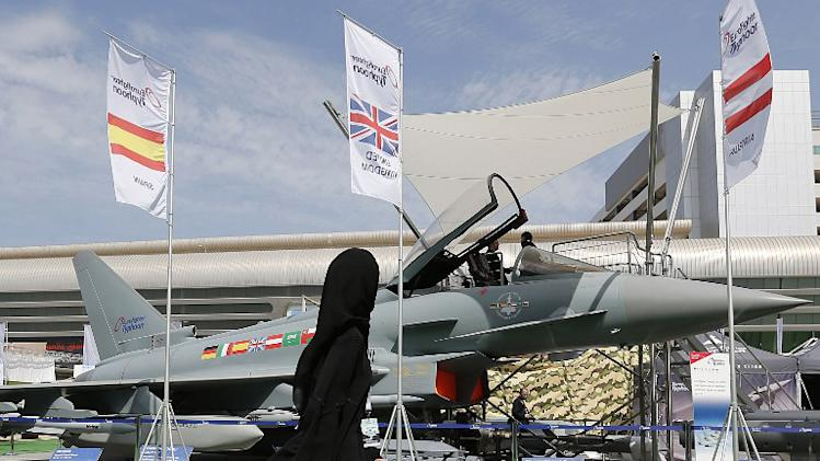 A woman walks past a Eurofighter Typhoon aircraft on display at a military show launching the International Defence Exhibition and Conference (IDEX) at the Abu Dhabi National Exhibition Centre in the Emirati capital on February 17, 2013.