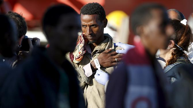 Member of police takes a picture of a migrant after disembarking from tug boat Asso29 in the Sicilian harbour of Pozzallo, southern Italy