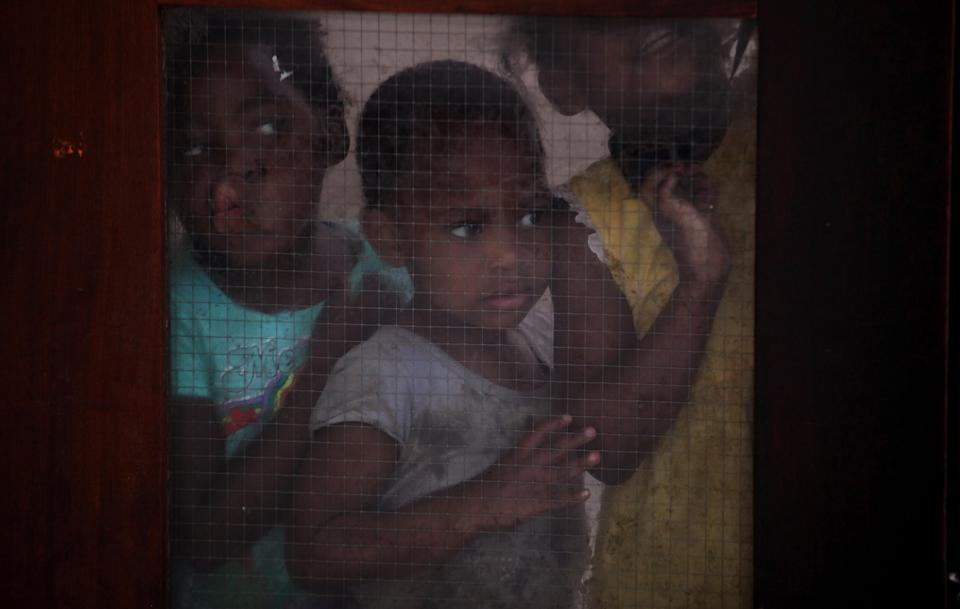 Children look through a glass door inside the dilapidated Central Methodist Church in downtown Johannesburg Wednesday, Dec. 31, 2014. The church has...