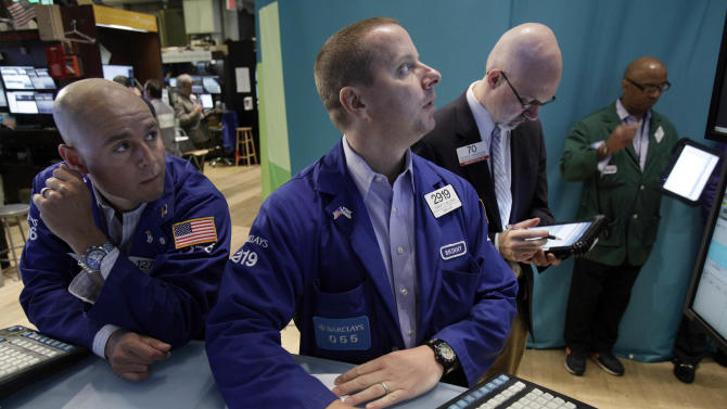 Specialists Mario Picone, left, and Robert Nelson, center, work at their posts on the floor of the New York Stock Exchange Friday, Aug. 3, 2012. U.S. stocks are rising sharply on Wall Street after a July jobs report revealed the strongest hiring trends in five months. (AP Photo/Richard Drew)