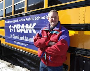 Marc Horner, fleet manager for Jeffco Public Schools, stands next to a school bus last year with a bank advertisement on its side at the school's bus maintenance facility in Lakewood, Colo. About half a dozen states already allow bus advertising _ including Colorado, Arizona, Florida, Minnesota, Tennessee and Texas. (AP Photo/Ed Andrieski)