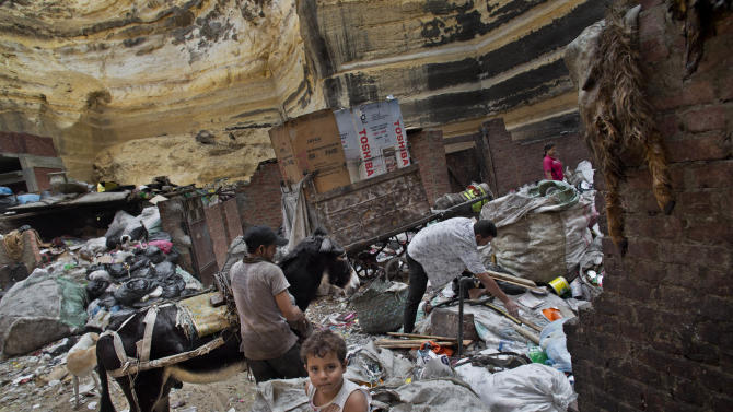 """In this Wednesday, Nov. 7, 2012 picture, an Egyptian family works in the Moqattam area in Cairo, Egypt, where more than 60,000 Coptic Christians known as the Zabaleen, or """"garbage people,"""" collect, separate, sell or reuse the city's trash. Egypt's Christian minority, about 10 percent of the population of more than 80 million, has long complained of discrimination. But Christians fear things are reaching a crisis point since the ouster of President Hosni Mubarak nearly two years ago and the subsequent rise to power of Islamists. The Church itself is undergoing a major transition: A new pope, Tawadros II, is to be enthroned in Cairo on Sunday, succeeding Shenouda III, the man who led the Church for 40 years and was revered by Copts as their protector until his death in March. (AP Photo/Bernat Armangue)"""