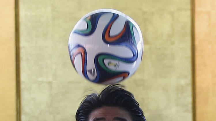 Japan's Prime Minister Shinzo Abe heads the ball during a meeting with Brazilian soccer players in Brasilia