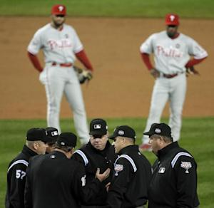 FILE - In this Oct. 28, 2009, file photo, Philadelphia Phillies' Pedro Feliz, left, and Jimmy Rollins watch in the background, as umpires discuss a call at first base during the fifth inning in Game 1 of the baseball's World Series against the New York Yankees in New York. Major League Baseball announced Thursday, Jan. 16, 2014, that it will greatly expand instant replay to review close calls starting this season. Each manager will be allowed to challenge at least one call per game. If he's right, he gets another challenge. After the seventh inning, a crew chief can request a review on his own. (AP Photo/Julie Jacobson, File)