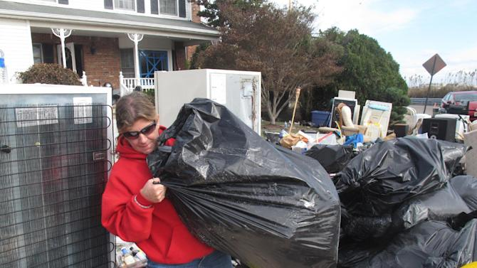 Laura DiPasquale sorts through bags of possessions that volunteers removed from her home in Point Pleasant Beach N.J. on Monday, Nov. 5, 2012. DiPasquale is frantically looking through them to see if well-meaning volunteers discarded anything she intended to keep before a second storm hits the shore on Wednesday, raising the possibility of renewed flooding and damage. (AP Photo/Wayne Parry)