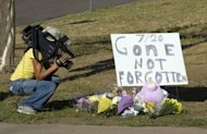 A cameraman takes video of a memorial for victims near the movie theater where 12 people were killed July 20, in Aurora, Colorado. Police on Saturday studied ways to enter an apartment rigged with explosives belonging to the man believed to have killed 12 moviegoers at an opening of the latest Batman movie