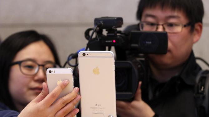 A Chinese television crew films an iPhone 6 and an iPhone 6 Plus after it went on sale at the Apple store in Sydney