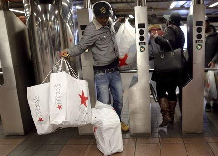 Shoppers enter the Herald Square Subway station after early morning Black Friday Shopping in New York