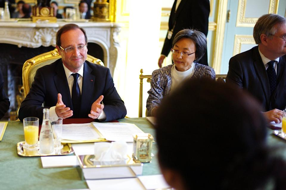 French President Francois Hollande, left, gestures prior to a meeting with Thailand's Prime Minister Yingluck Shinawatra, from behind, at the Elysee Palace, in Paris, Friday, July 20, 2012. (AP Photo/Thibault Camus, Pool)