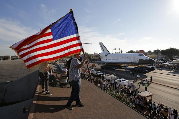 Roni Lopez, center, holds an American flag as the Space Shuttle Endeavour slowly moves along city streets on a 160-wheeled carrier in Los Angeles, Saturday, Oct. 13, 2012 towards the California Scienc