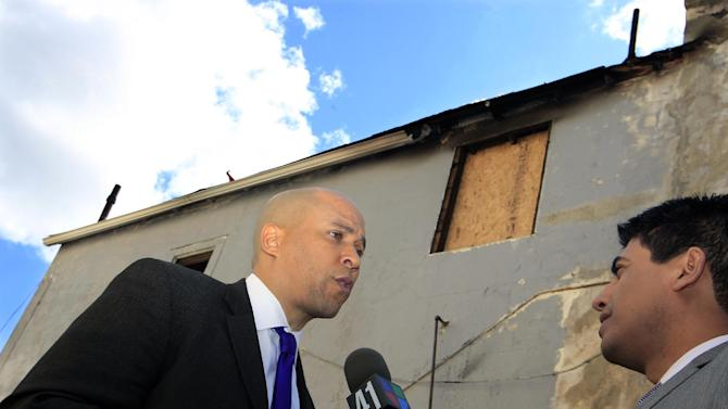 Newark Mayor Cory Booker has a bandaged right hand as he answers a question next to a burned home in Newark, N.J., Friday, April 13, 2012, where he was credited with rescuing a neighbor Thursday from a fire. Booker said Friday he feared for his life as he helped rescue a neighbor from a fire before firefighters arrived. He described how he returned home Thursday night and saw his neighbor's home engulfed in flames. The woman Booker helped save is in stable condition. (AP Photo/Mel Evans)