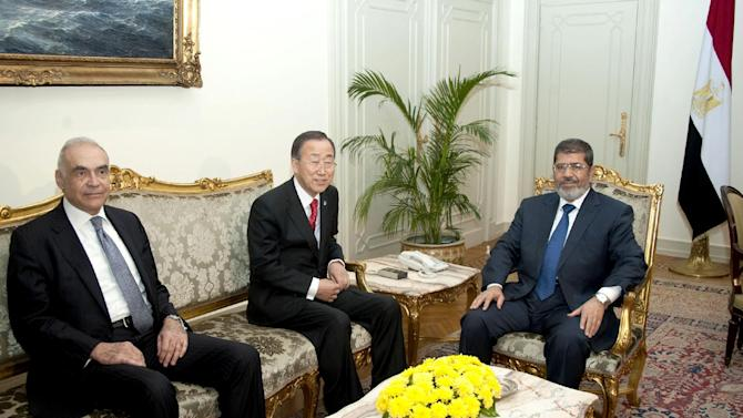 In this photo released by the Egyptian Presidency, U.N. Secretary-General Ban Ki-moon, center, poses for photographers during his meeting with Egyptian Foreign Minister Mohammed Kamel Amr, left, and President Mohammed Morsi, right, in Cairo, Egypt, Wednesday, Nov. 21, 2012. Israel and Hamas agreed to a cease-fire Wednesday following a swirl of diplomatic activity also involving U.N. chief Ban Ki-moon and Egypt's Morsi.(AP Photo/Egyptian Presidency)