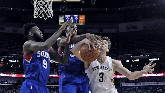 CORRECTS IDENTIFICATION- New Orleans Pelicans center Omer Asik (3) battles under the basket with Philadelphia 76ers guard JaKarr Sampson and center Henry Sims, in the first half of an NBA basketball game in New Orleans, Monday, Jan. 26, 2015. (AP Photo/Gerald Herbert)