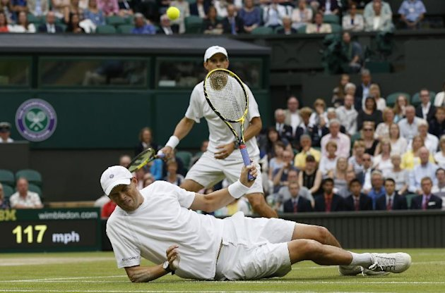 Bob Bryan, front, slips on the grass during the Wimbledon men's doubles final. (AP Photo/Sang Tan)