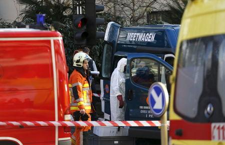 A Belgian firefighter and an expert investigate outside the Grand Mosque in Brussels
