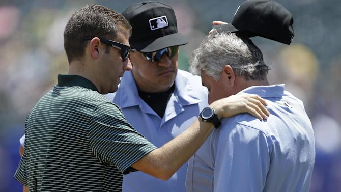 Home plate umpire Tom Hallion, right, is examined by Oakland Athletics trainer Brian Schulman after Hallion was hit by a baseball in the first inning of a baseball game against the Colorado Rockies Wednesday, July 1, 2015, in Oakland, Calif. Hallion left the game. (AP Photo/Ben Margot)