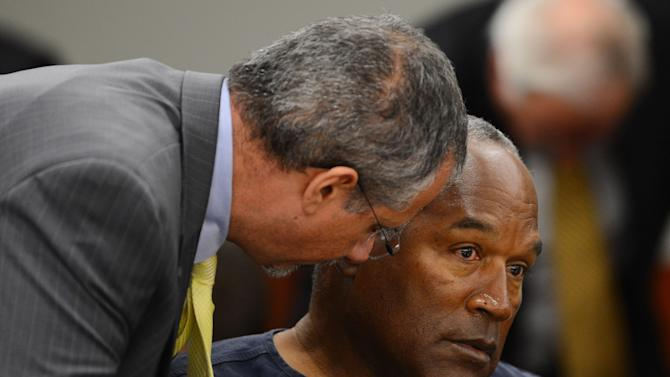 Defense attorney Ozzie Fumo, left, confers with his client, O.J. Simpson during an evidentiary hearing for Simpson in Clark County District Court on Tuesday, May 14, 2013 in Las Vegas.  The hearing is aimed at proving Simpson's trial lawyer, Yale Galanter, had conflicted interests and shouldn't have handled Simpson's case. Simpson is serving nine to 33 years in prison for his 2008 conviction in the armed robbery of two sports memorabilia dealers in a Las Vegas hotel room. (AP Photo/Ethan Miller, Pool)