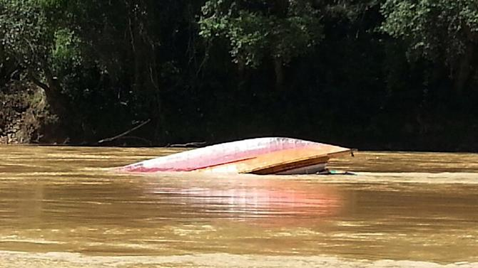 In this photo taken by Belaga state assemblyman Liwan Lagang, the capsized boat floats in a river of Sungai Rajang in Belaga in the state of Sarawak on the Borneo island, Malaysia, Tuesday, May 28, 2013. An overloaded ferry capsized after hitting rocks in a remote river leaving 21 people missing and feared trapped inside the vessel, police said. Another 181 survivors swam ashore or were rescued by villagers. (AP Photo/Liwan Lagang) EDITORIAL USE ONLY, NO ARCHIVE, NO SALES